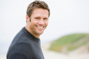 Man at beach, looking over shoulder, smiling