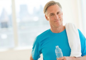mature man at a gym with bottled water