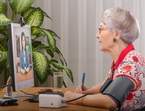 The patient shown here consults with a physician via telemedicine technology even as her blood pressure reading is taken and transmitted electronically to the doctor.