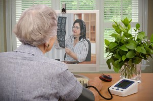 A patient interacts via video with a physician who is simultaneously checking out the results of the patient's recent CT scan.