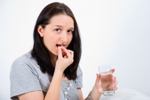 Young woman taking a pill and holding a glass with water,copy space for text message
