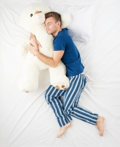 Sleeping on your side -- with or without a giant teddy bear -- is generally the most beneficial sleeping position for the spine.
