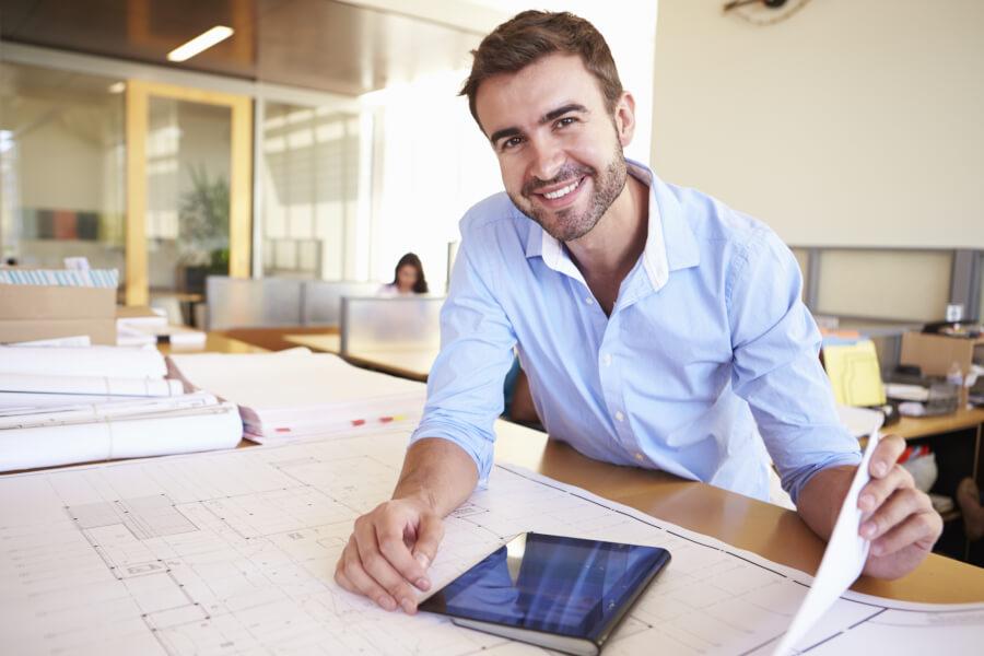 man sitting at desk, smiling