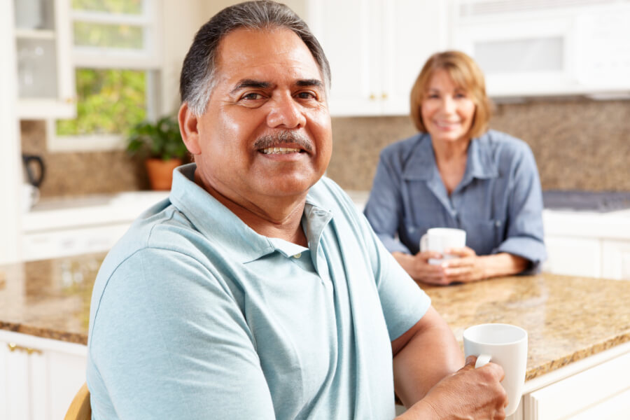 mature man having coffee with wife in kitchend