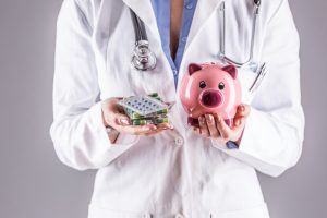 Medical doctor holding a piggy bank and pills.