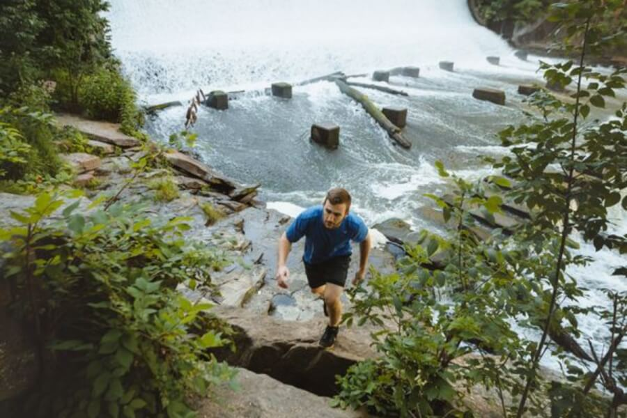 Man hiking with a waterfall in the background.