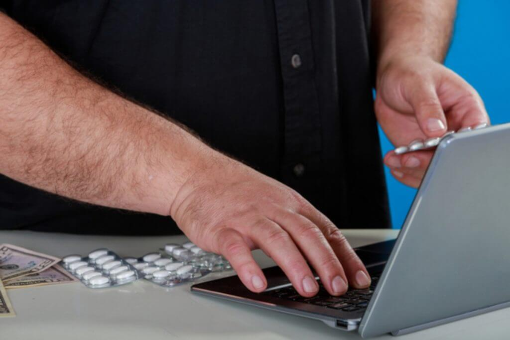 Person typing on a laptop holding pill packets.
