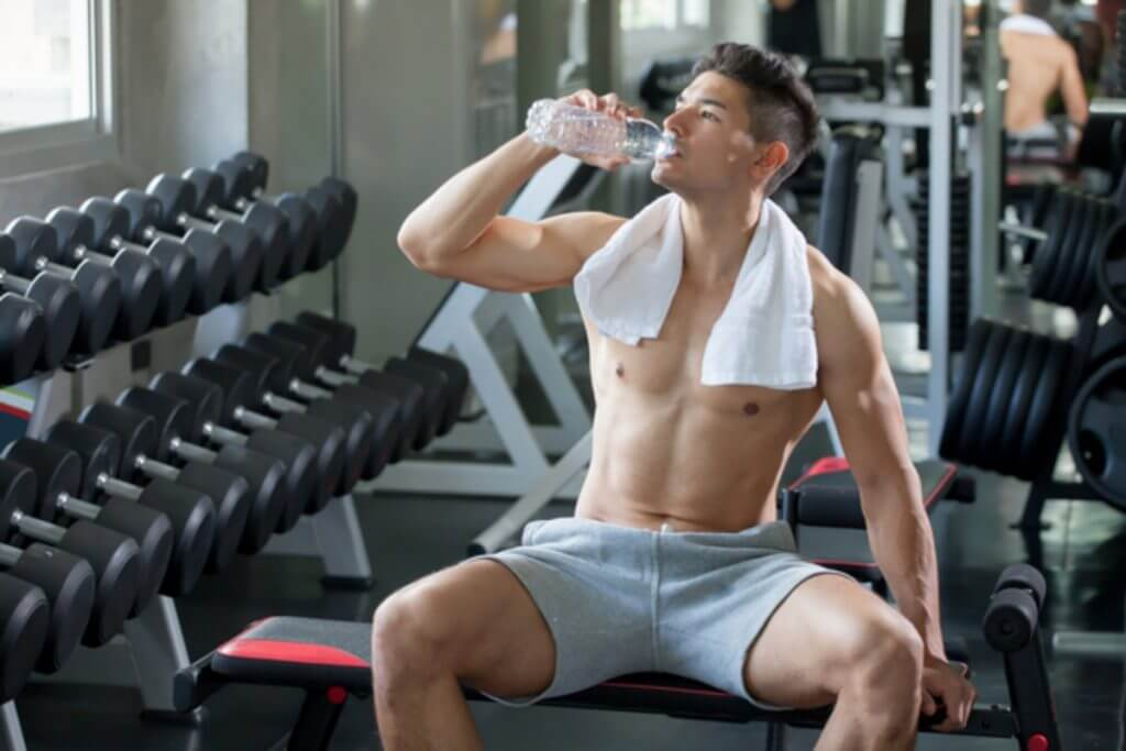 Man at the gym drinking a bottle of water.
