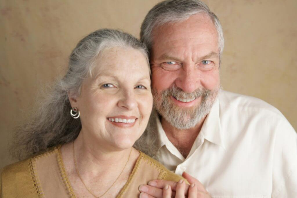 Older couple smiling.