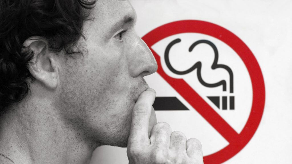 Man standing in front of a no smoking sign.