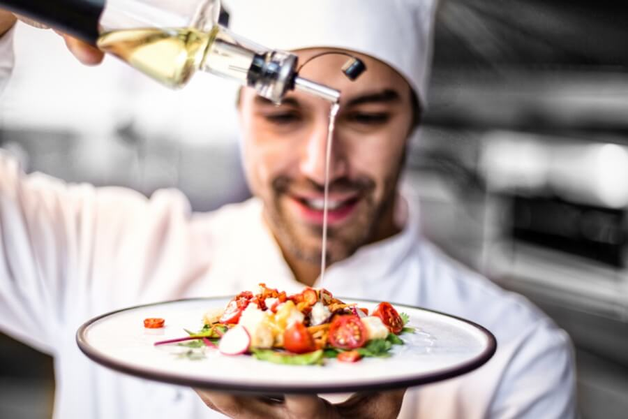 Chef pouring oil on a dish.