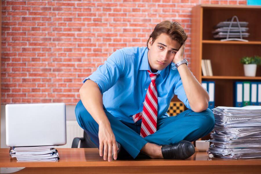 Businessman sitting onto of a desk.