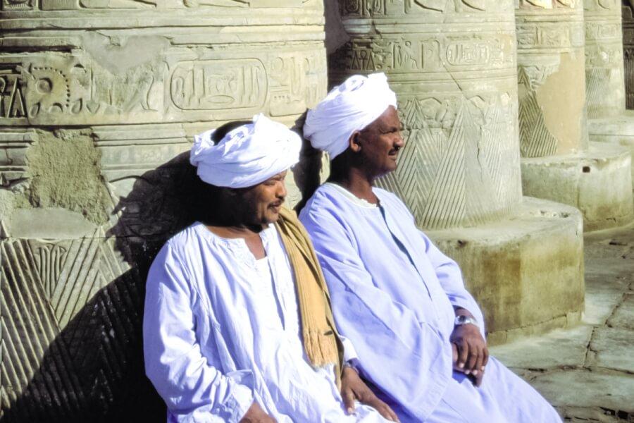 Two men sitting next to large columns.