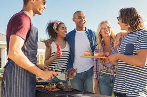 Group of people around an outdoor grille.