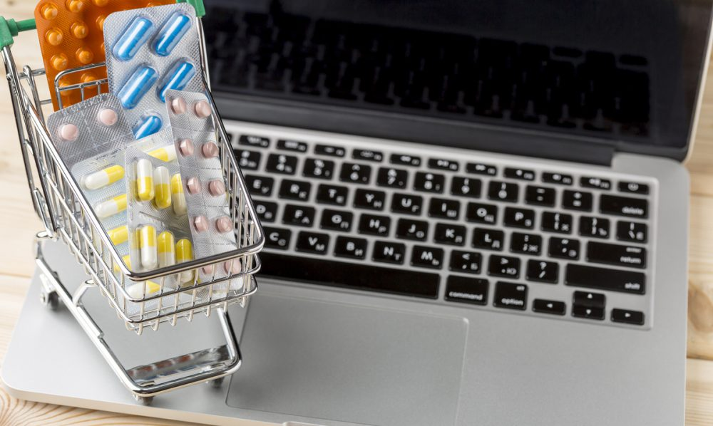 Laptop computer with miniature shopping cart filled with pills.