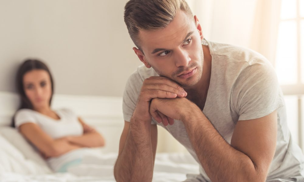 Man sitting on edge of bed looking disappointed.