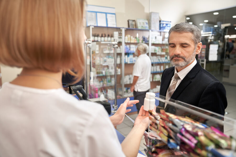 Man filling a prescription at a pharmacy.