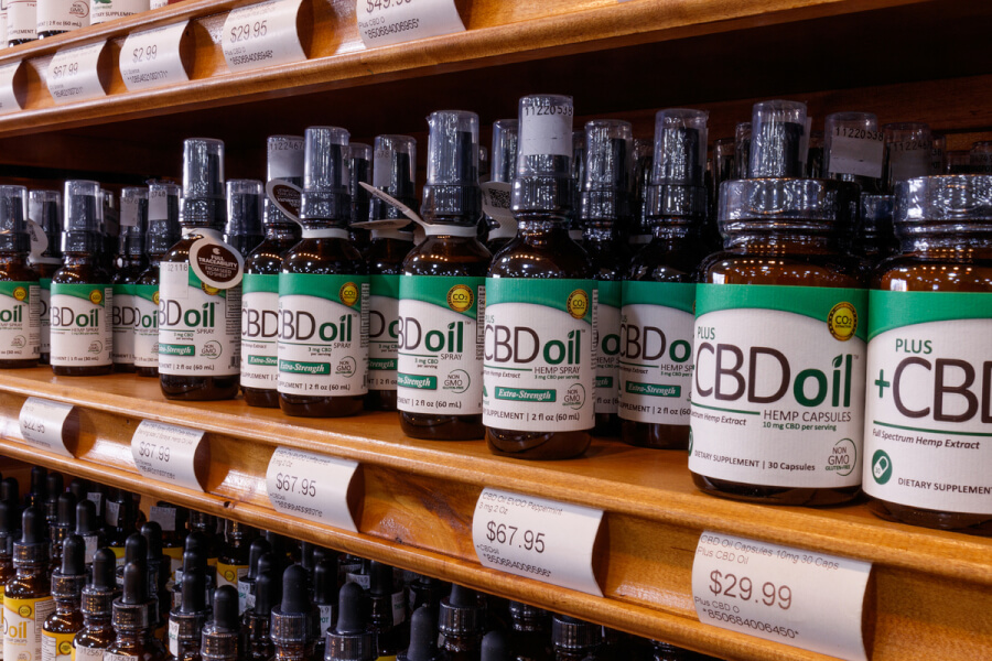 Bottles of CBD oil on a shelf in a store.