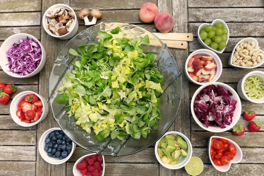 Table top with fresh salad, fruits and nuts.