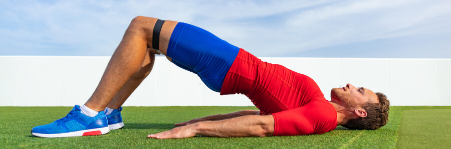 Man performing yoga on a green lawn.
