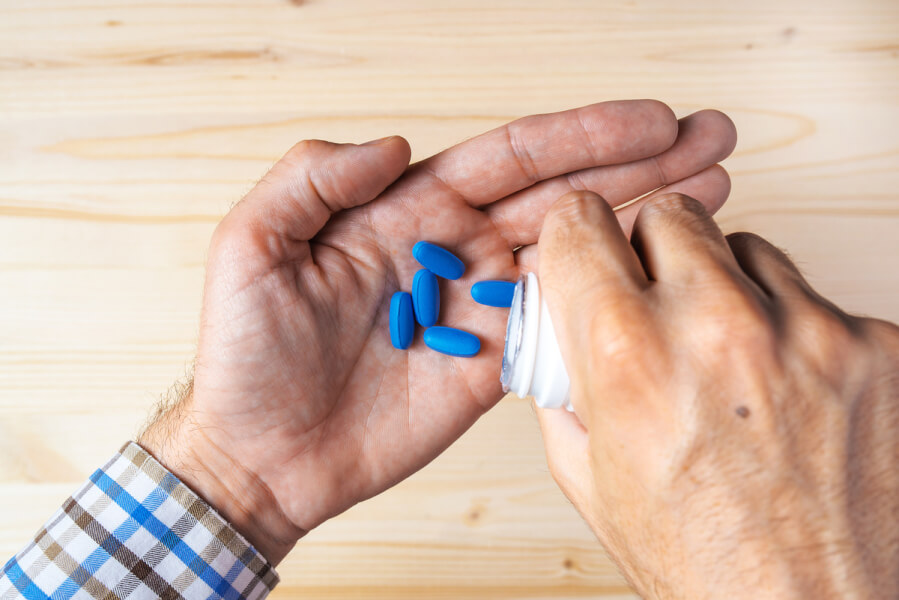 Person pouring blue pills into his hand from a plastic container.