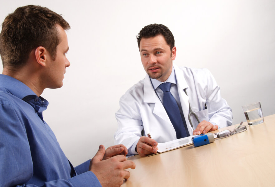 Medical doctor having a discussion with a male patient.
