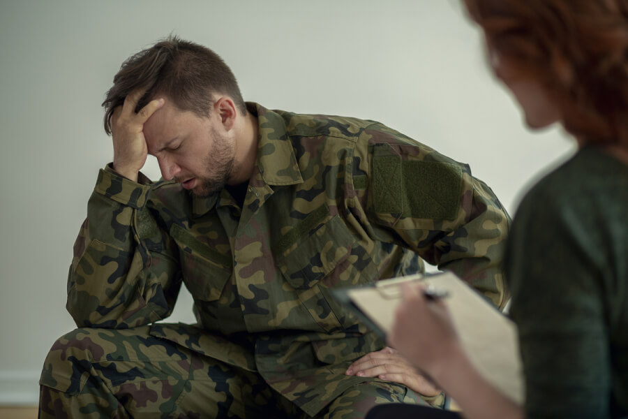 Man in military fatigues sitting with his hand on his head.