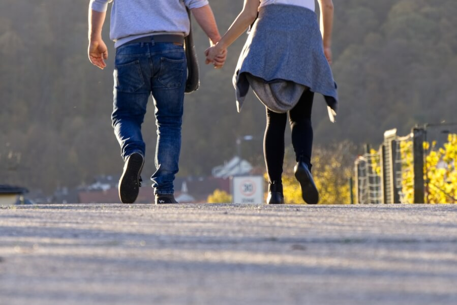 Two people walking holding hands.