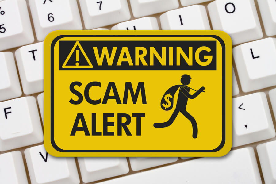 Yellow warning sign labeled Scam alert.