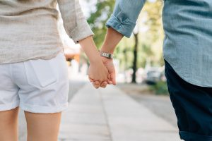 Couple holding hands while walking down the sidewalk.