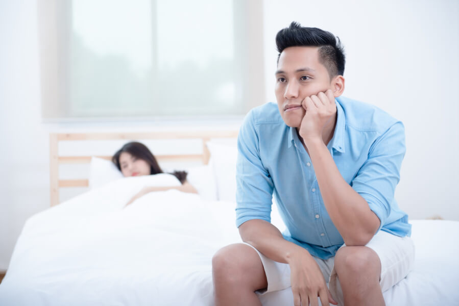 Man sitting at the end of his bed appearing frustrated.
