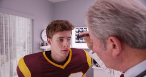 Medical doctor evaluating a football player.