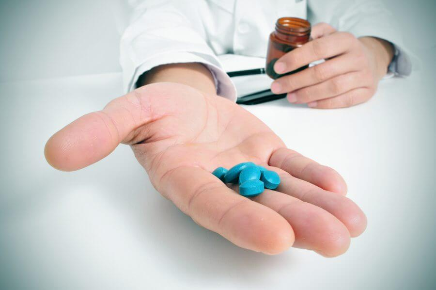 Person holding Viagra pills in their hand.
