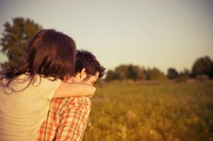 Couple outdoors hugging.