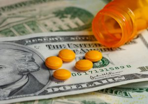 Orange pills on top of us paper money.