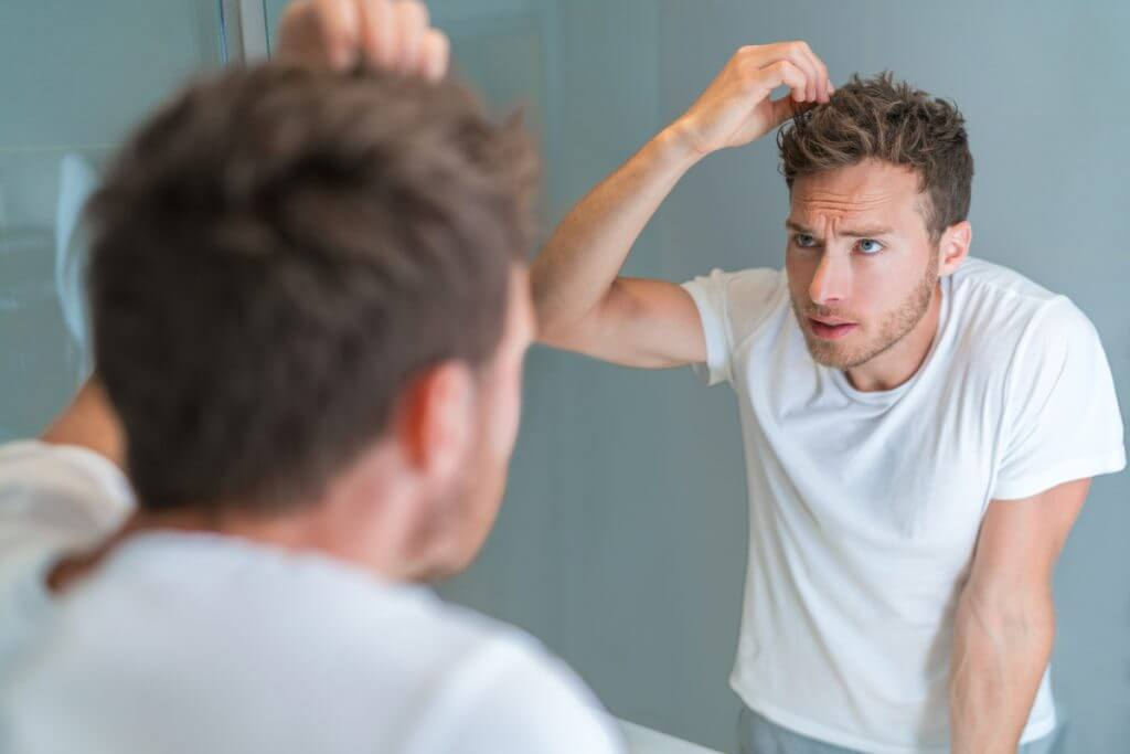 Man looking at his hair in a mirror.