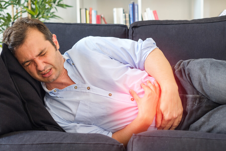 Man lying down with discomfort in his abdomen.
