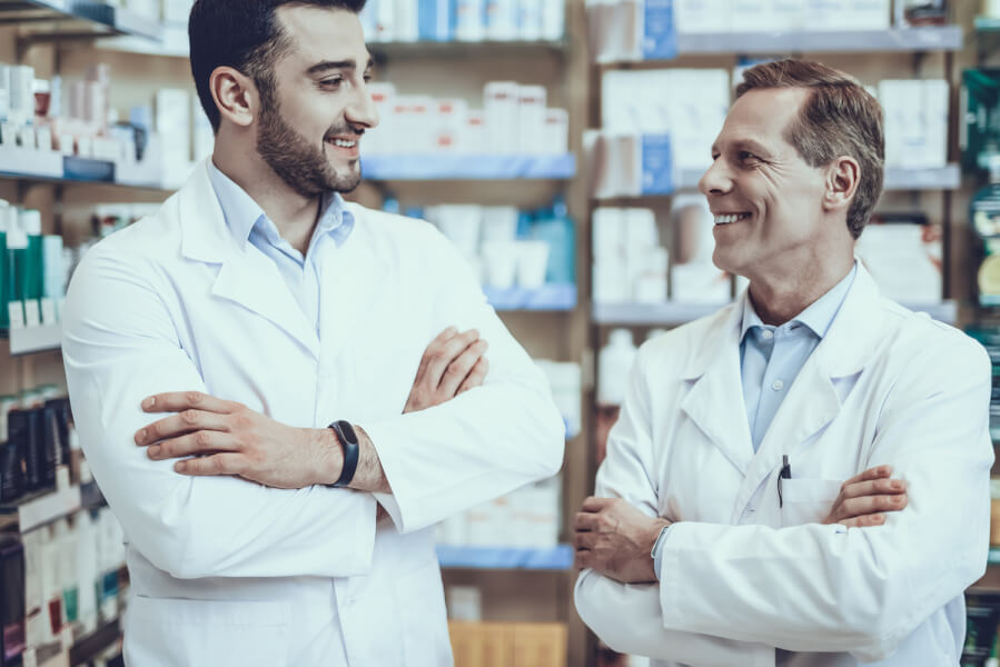 Two pharmacists standing next to each other smiling.