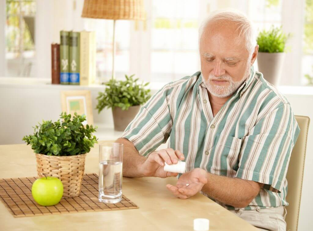 Older man sitting a a table taking a pill with a glass of water.