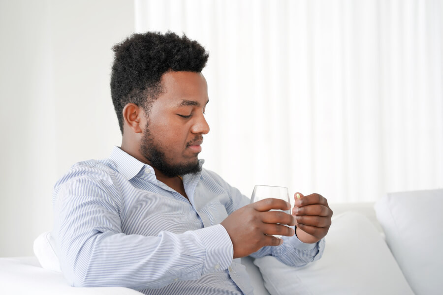 Man sitting on a couch taking a pill with a glass of water.
