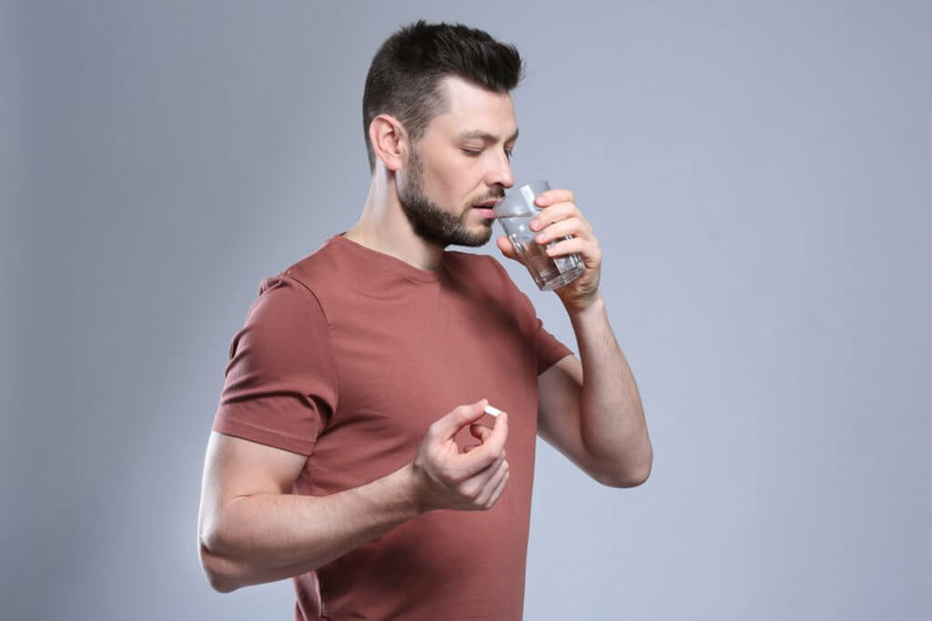 Man taking a pill with a glass of water.