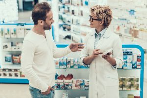 Man asking a pharmacist questions.
