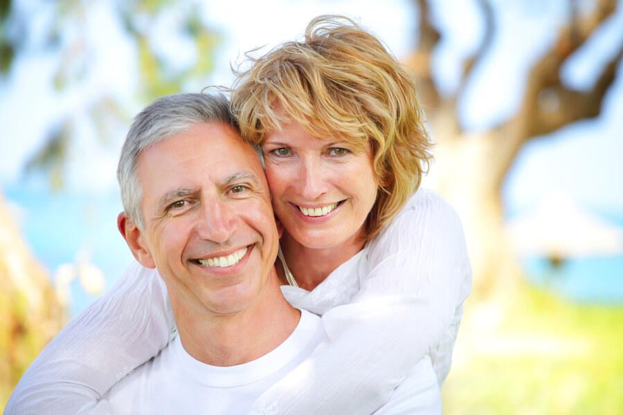 Happy couple hugging outside.