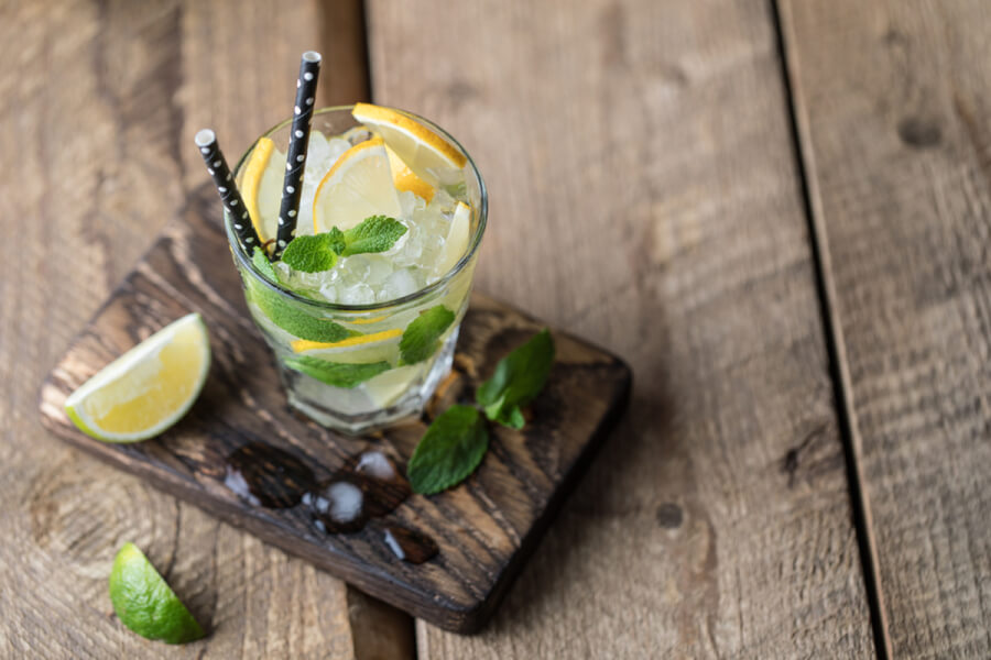 Alcoholic beverage in a glass with lemon and lime.