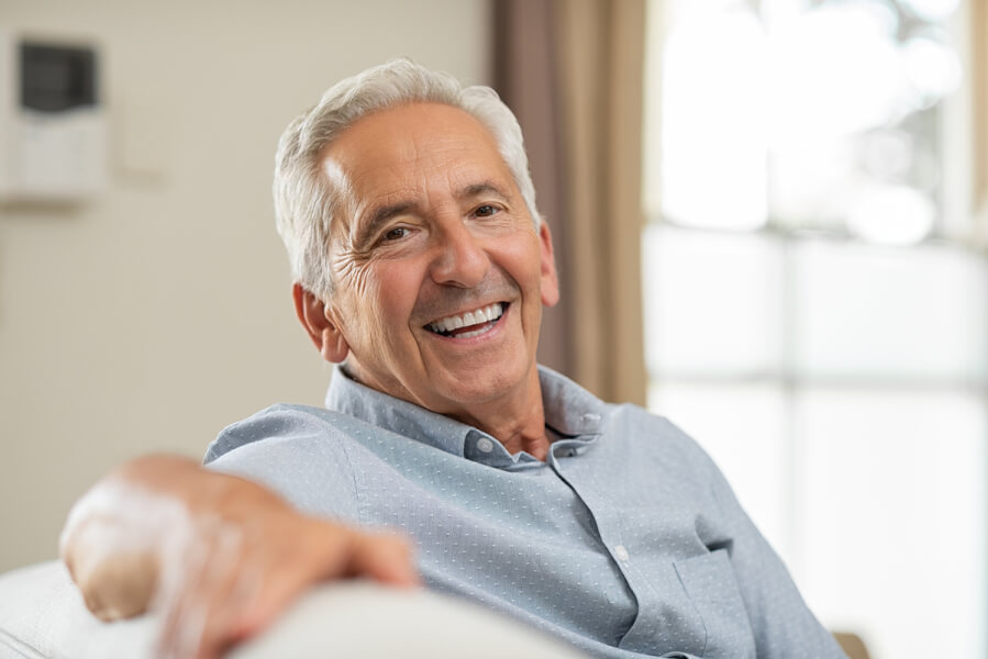 Man smiling while sitting on a couch.