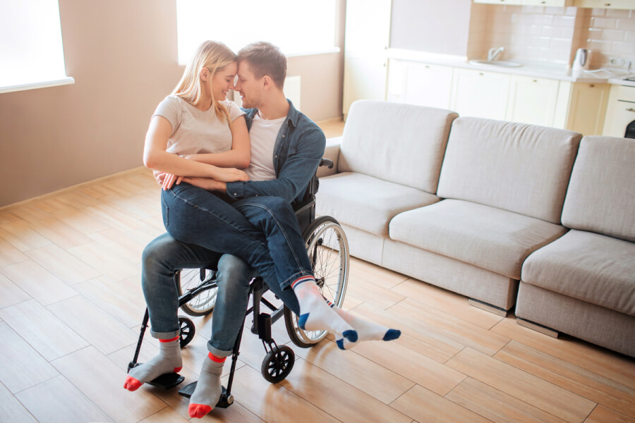 Man in a wheelchair with a woman on his lap.