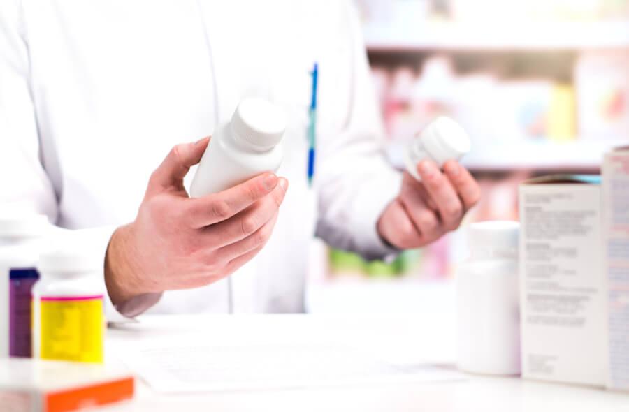 Pharmacist reading labels on pill bottles.