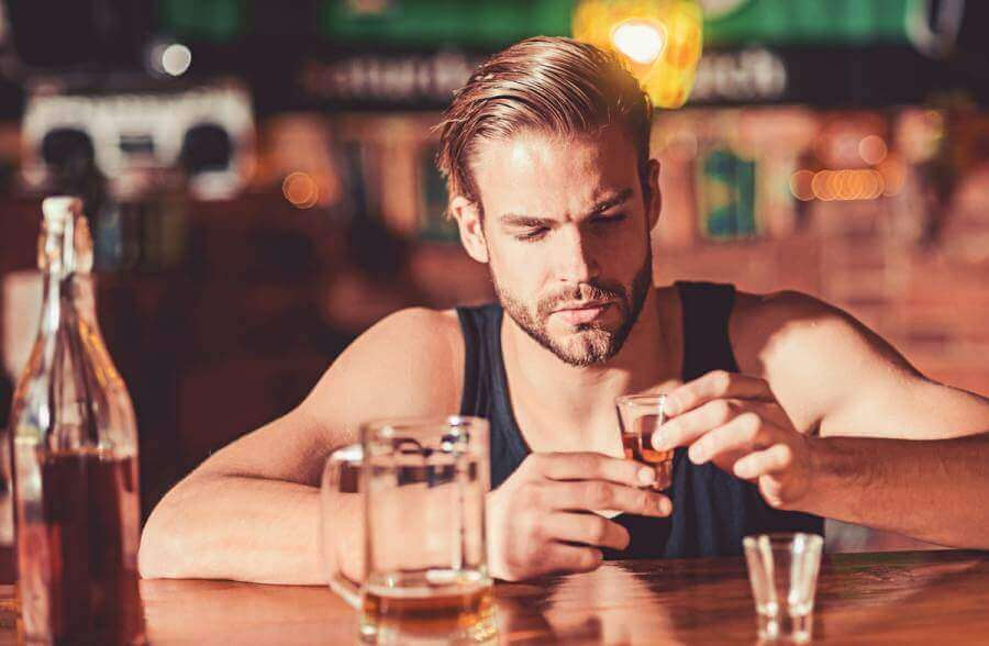Man sitting at a bar with a shot.