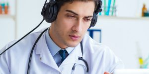 Medical doctor with headphones on a video telemedicine call.
