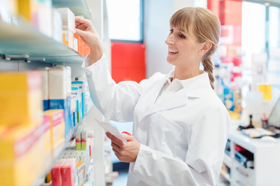 Medical pharmacist looking for medication on a shelf.